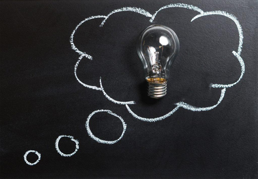 Ein Tafeloberfläche ist im Hintergrund. Mit Kreide ist eine GEdankenblase gezeichnet. In dieser ist eine echte Glühbirne. Dieses Bild soll für Mathematik und Informatik stehen.