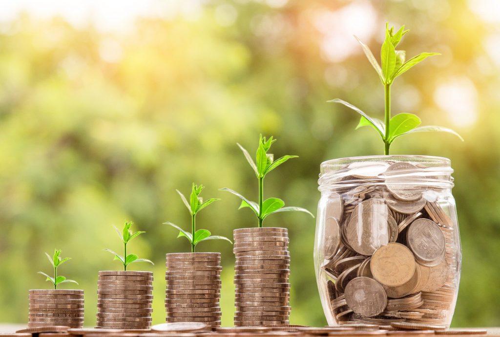 Geldmünzen in Stapeln von klein nach groß. Als letztes ein Glas voll mit Münzen. Auf jedem Münzstapel wachst eine kleine Pflanze.  Dieses Bild soll Wirtschaft darstellen.